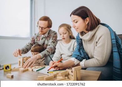 Young mom and dad play educational games with children