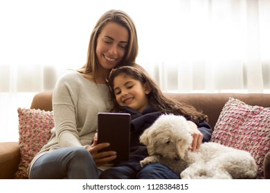 Young mom, daughter and dog sitting on the sofa looking a tablet