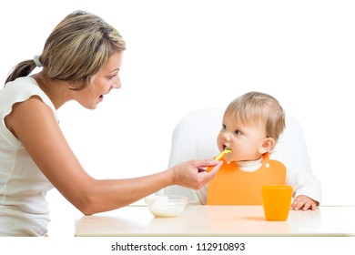 young mom feeding her happy baby girl with help of spoon
