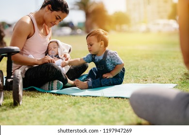 Young mom in fitness wear sitting in park with her kids. Woman sitting with her kids on grass early in the morning with sunflare in the background.