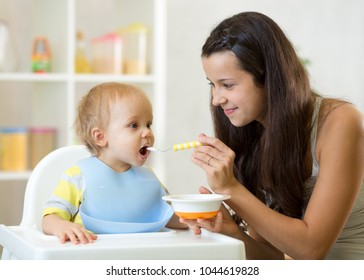 Young mom giving homogenized food to her baby son on high chair in kitchen.