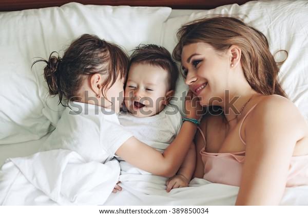 La madre joven con su hija de 5 años y su bebé de 4 meses vestidos con pijama están relajándose y jugando juntos en la cama el fin de semana, mañana perezosa