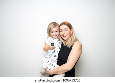 young mom mother baby girl pose white background remote control camera happy
