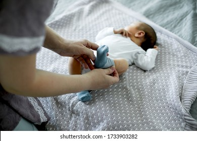 Young mom mother dresses her newborn baby boy on bed in bedroom at home. Lifestyle. Motherhood concept