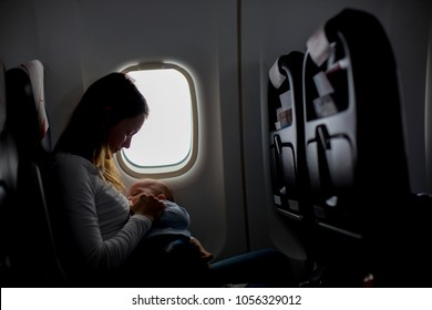 Young mom, playing and breastfeeding her toddler boy on board of aircraft, going on holiday