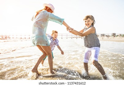young mom is playing with her children on the beach