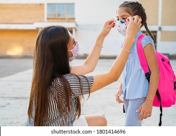 Young mom putting on mask to her daughter before school / or safely removing
