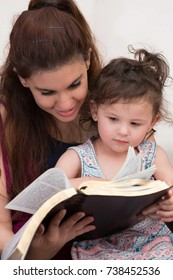Young Mom Reading the Holy Bible to Her Little Daughter