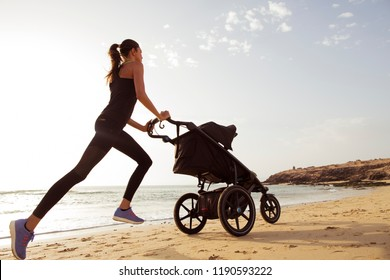 Young mom is running with stroller on the beach.