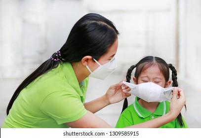 Young mom wearing protective mask for her daughter while outside to against PM 2.5 air pollution in Bangkok city. Thailand.