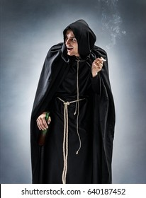 Young monk with bottle of wine and cigarette. Photo of a drunken monk on gray background. Religious concept
