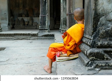 Young monk seated in Angkor wat temple,Cambodia
