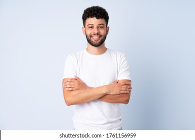Young Moroccan man isolated on blue background with arms crossed and happy