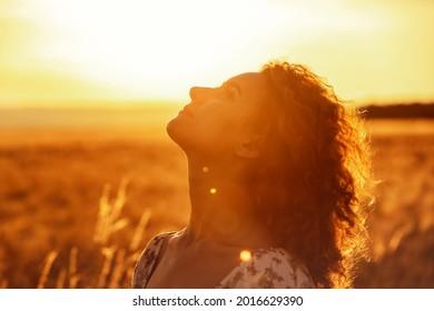 junge Marokkanerin mit braunem, lockerem Haar, die auf einem Weizenfeld steht, während die Sonne im Hintergrund untergeht und die Kamera blendet