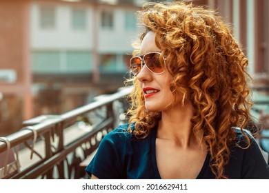 junge Marokkanerin, mit lockbraunem Haar, in einem Café im Freien in Mainz, mit Sonnenbrille