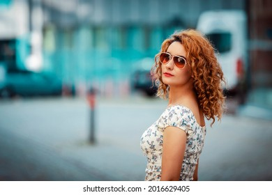 junge Marokkanerin mit lockigen Haaren, mit Sonnenbrille tragen, sich der Kamera zuwenden, in einer städtischen Umgebung