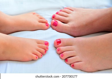 Young mother (30) and her girl child daughter (4 years old) compare the size of their painted nail polish feet.
