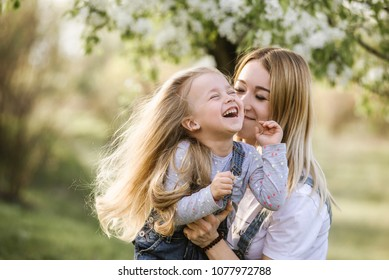 young mother with adorable daughter in park with blossom tree. Happy mother and child