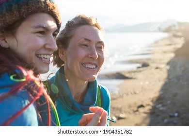 young mother and adult daughter laugh while walking and traveling along the seashore. the attitude of mom and daughter. two women are having a good time in nature. lgbt.