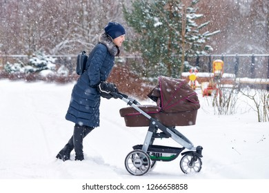 Young mother with a baby carriage in the park during snowfall