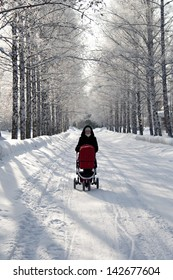 young mother with baby carriage in winter forest