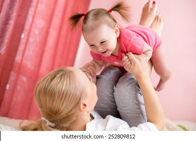 Young mother with baby have fun doing exercise, leisure - concept