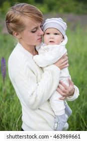 Young mother with baby at meadow lupins flowers