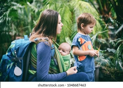 A young mother with a baby in a sling and little boy is walking in the jungle