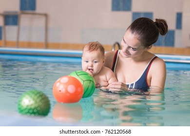 Young mother with baby in swimming pool. Woman holding a toddler while having fun in water