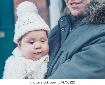A young mother and baby in winter clothes outside the house