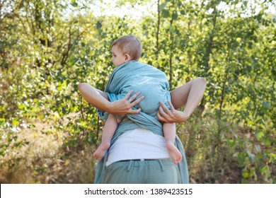 Young mother babywearing one year old son in a park, adjusting the sling.