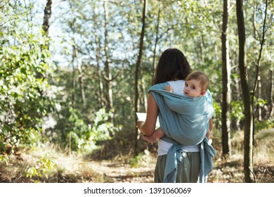 Young mother babywearing one year old son in a park.
