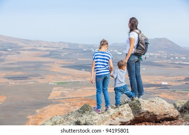 Young mother with backpack and her chid standing on cliff's edge and looking to a sky