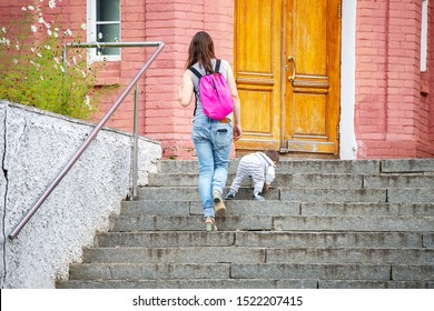 a young mother with a backpack on her back climbs the stairs after her young son, who climbs the stairs on his own during a walk in the fresh air