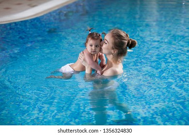 young mother bathes the baby in the pool