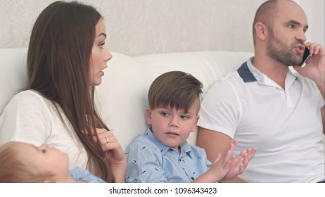 Young mother being angry with her husband talking on the phone and not playing with his sons