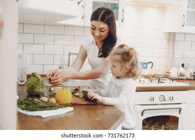 A young mother with black hair is preparing food at home in the kitchen with her little daughter