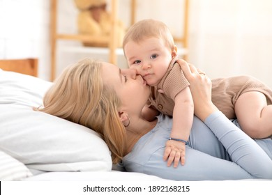 Young mother blonde woman kissing sweet little baby, cute kid laying on mom belly and looking at camera while parent kissing him or her, home interior, copy space, side view. Family, parenthood conept