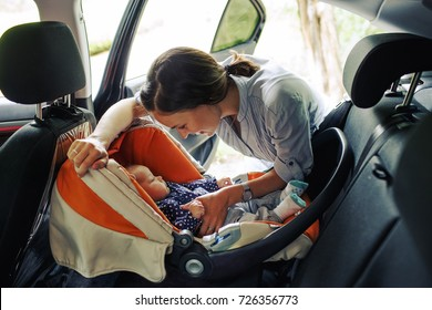 Young mother in blue shirt looking at the baby seating in orange car chair