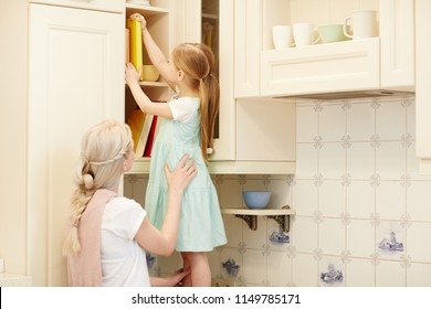 Young mother with braid supporting daughter and keeping her while cute girl in dress putting book on shelf of kitchen set and standing on counter