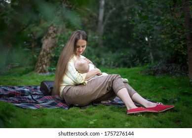 Young mother breast feeding her baby on nature background. Breast-feeding. Motherhood and care concept.
