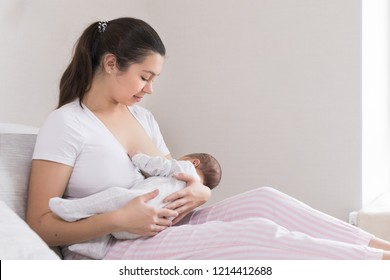 Young mother breast feeding, nursing and hugging baby. Mom breastfeeding her newborn son. mother breastfeeding and hugging her infant boy