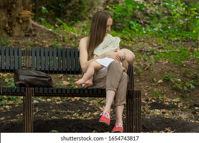 Young mother breastfeeding baby in the park. Mom sits on bench and holds tiny tot in arms