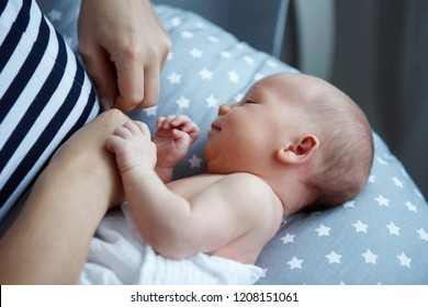 A young mother is breastfeeding her seven-day-old daughter. Close-up. The concept of natural feeding, healthy eating.