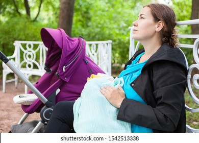 Young mother breastfeeds her baby in the park, covering him with blanket, sits on a bench near the stroller