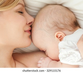 Young mother breastfeeds her baby. Breast-feeding.