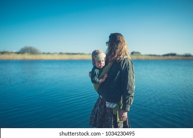 A young mother is carrying her baby in a sling by the water in winter