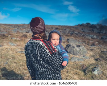 A young mother is carrying her baby in a sling on the moor
