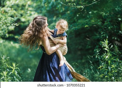 Young mother carrying her baby girl in a sling. Shot on location in a park with natural light.