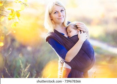 Young mother carrying her baby in a shawl sling. Shot on location with natural light. Autumn season